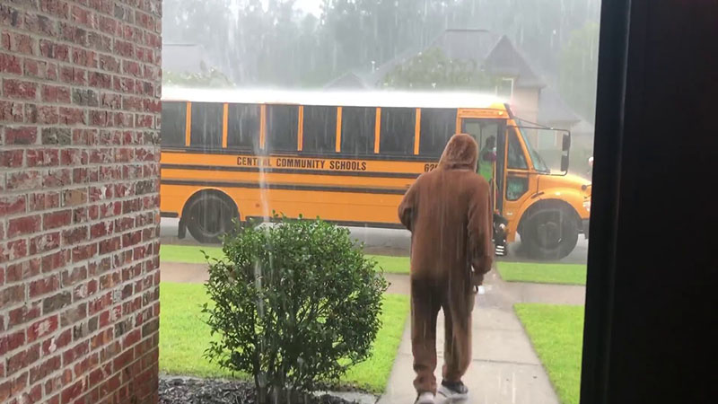 Noah walks into the rain in a fuzzy brown bodysuit to get Max from the bus