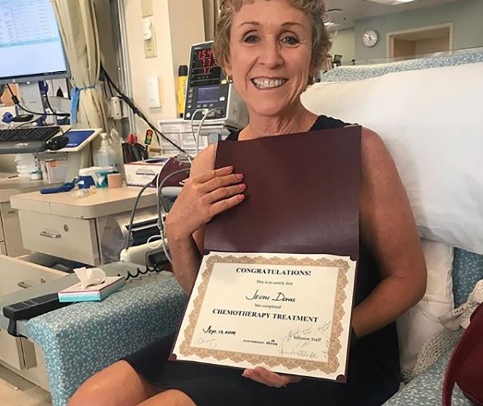 Cancer survivor holds a certificate marking the end of chemotherapy
