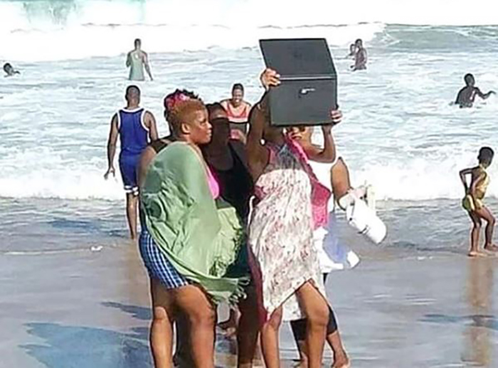 Women hold up a laptop for a selfie at the beach
