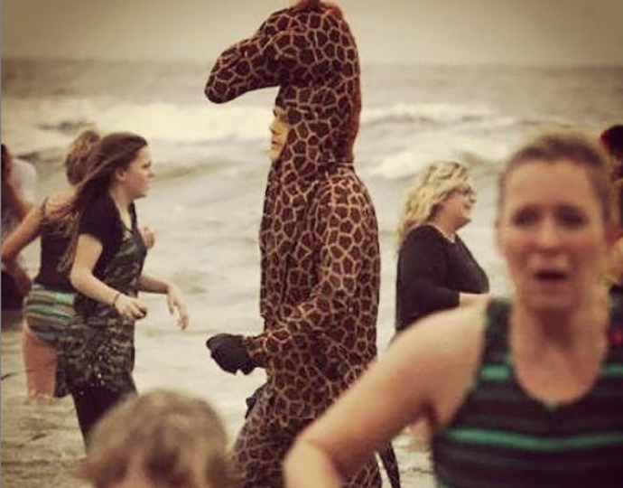 People run away from a man in a giraffe costume