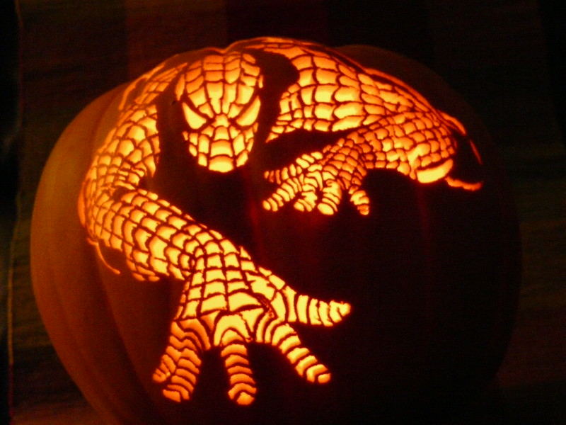 A pumpkin is carved so that it appears that Spiderman is climbing over it.