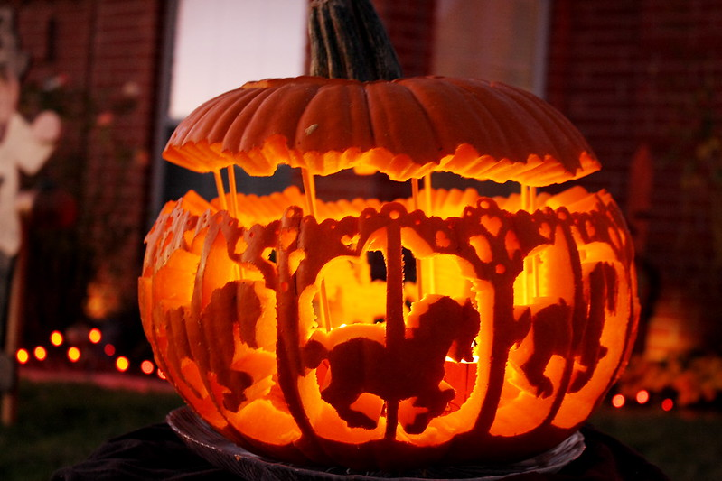 A pumpkin is carved to look like a carousel.
