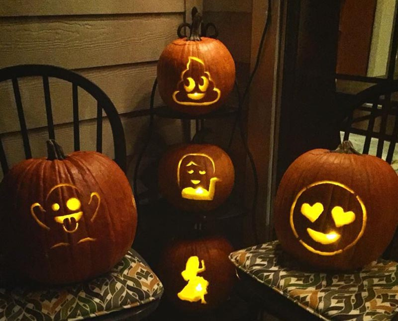 Four pumpkins are carved to look like various emojis.