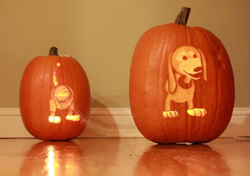 Two pumpkins are carved to look like to halves of a dog and are joined with a slinky.