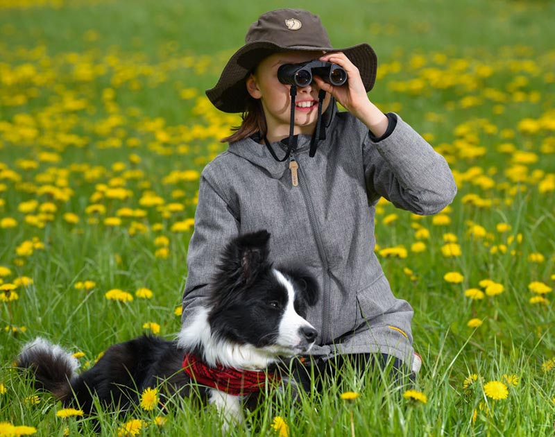 A girl looks through her binaculars while seating in a grass field with her border collie.
