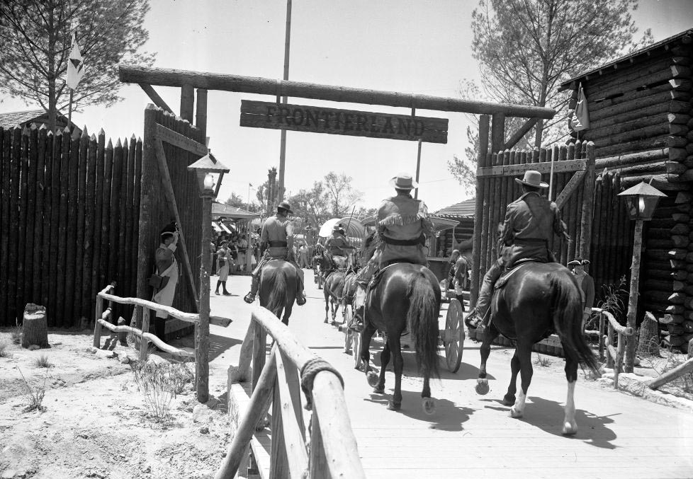 Men ride horseback into Frontierland.