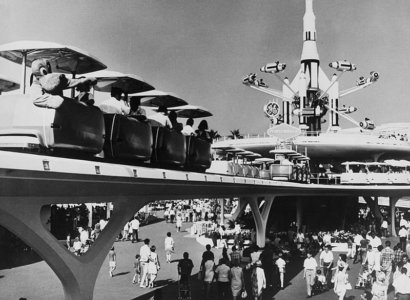 Crowds pass beneath the tram in Tomorrowland.
