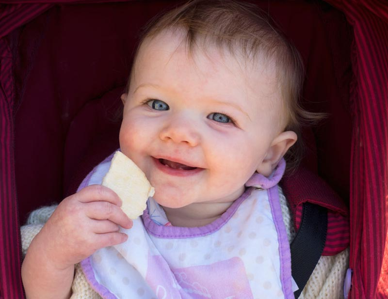 A baby smiles while holding a snack near her mouth.