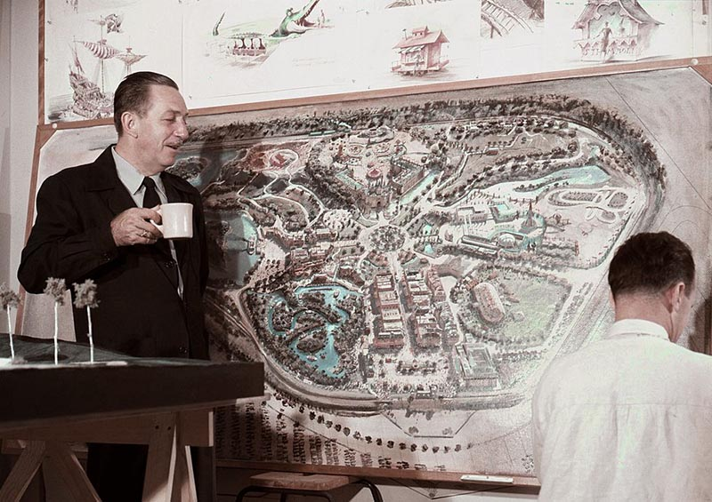 Walt Disney stands before a map of Disneyland.