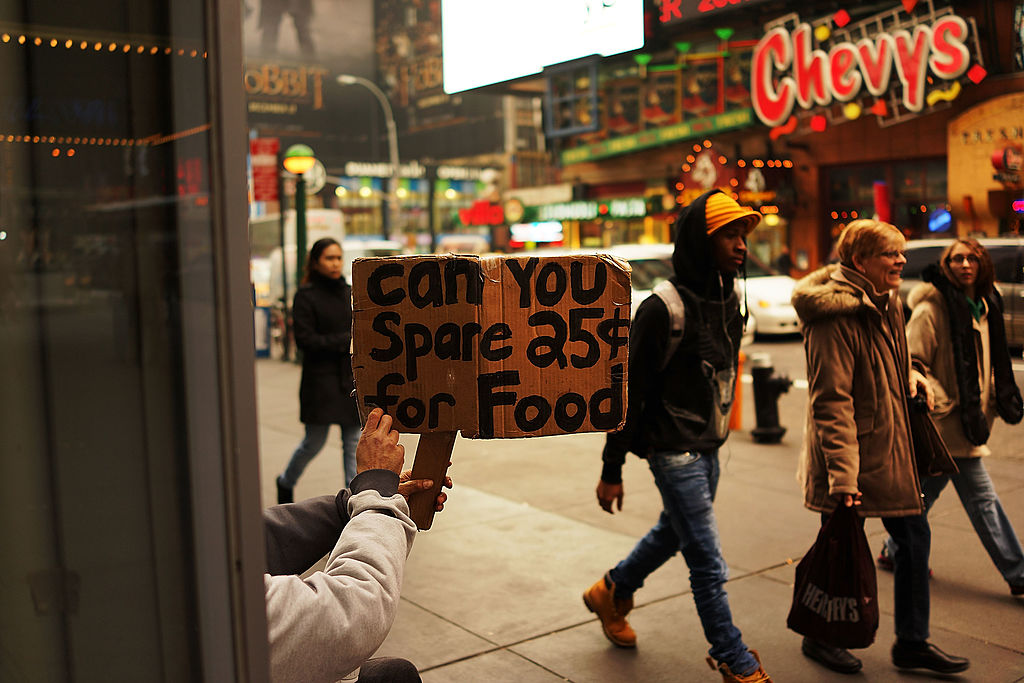 A homeless person holds up as passersby ignore her.