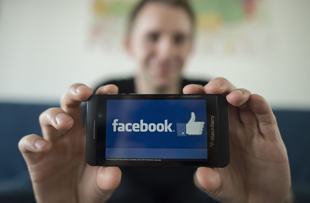 A man holds up the Facebook logo on his cell phone.