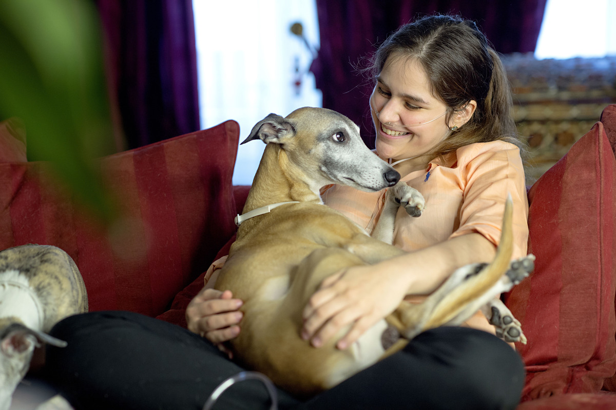 Girl with nasal cannula sits on a sofa and holds her Greyhound in her arms.