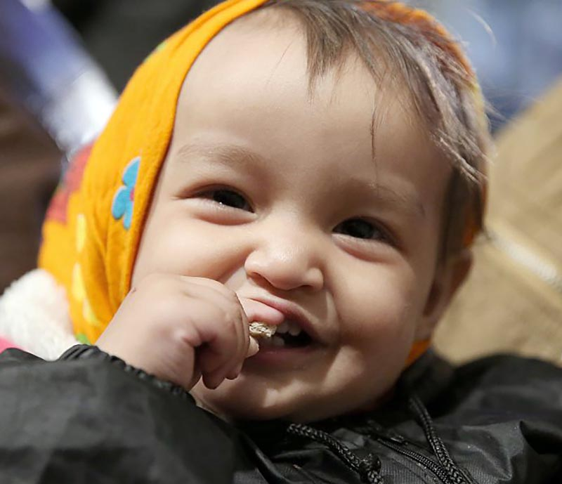 A baby smile while taking a bite of something.