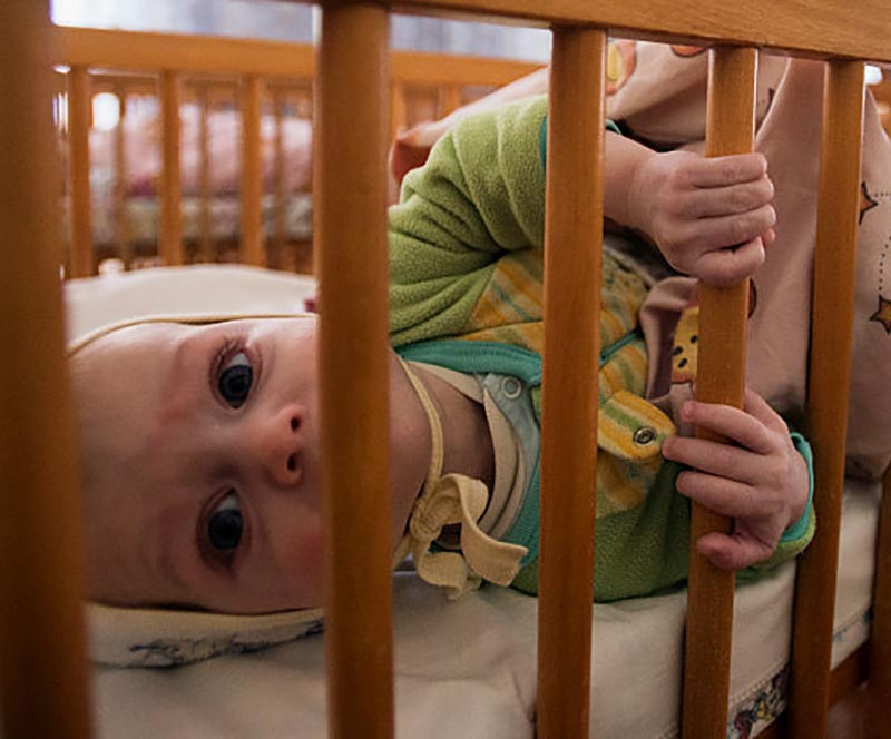 A baby peers through its crib.