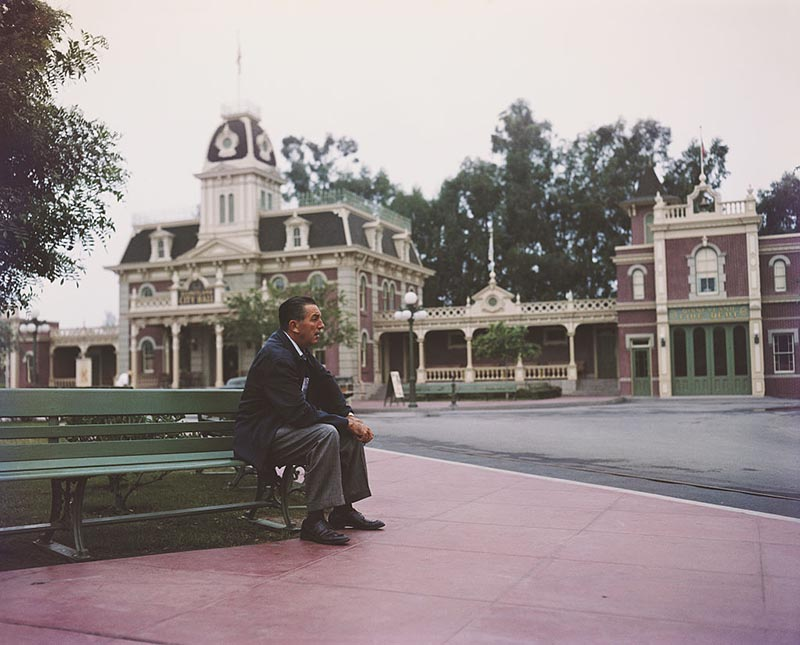 Walt Disney sits on a bench in an empty Disneyland.