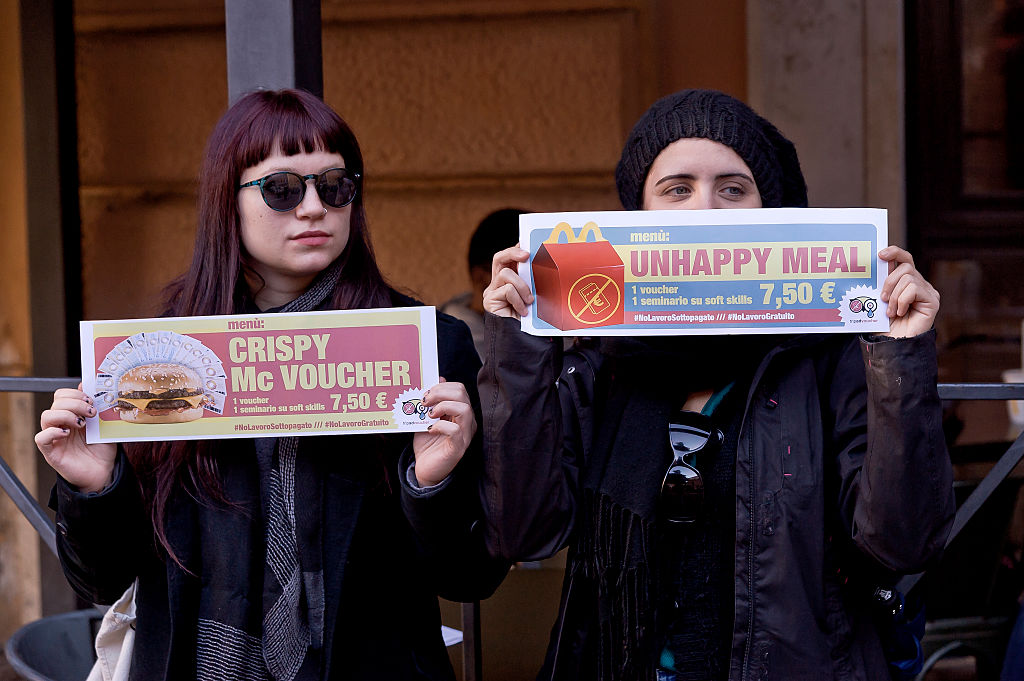 Two women hold signs protesting McDonald's vouchers.