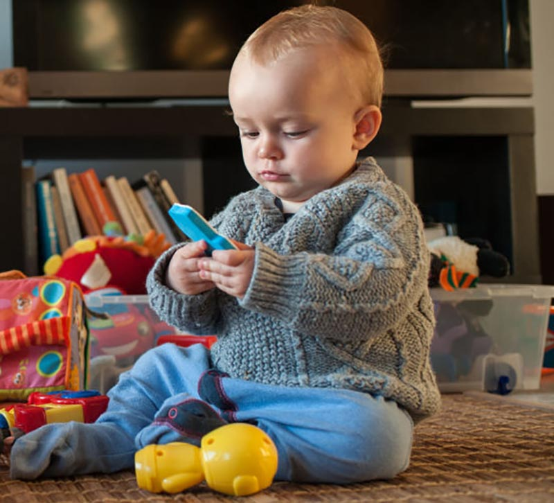 A baby plays with his toys on the living room floor.