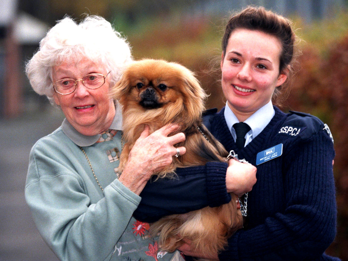 Two women hold up Gizmo, a three-year-old Tibetan Spaniel