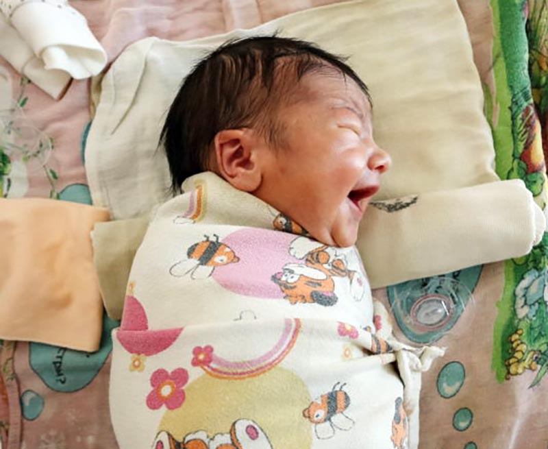 A baby with closed eyes wears a large smile.