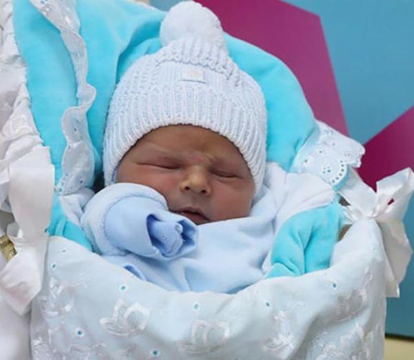 A sleeping baby is heavily bundled.
