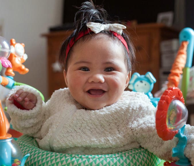 A baby smiles while standing in a jumper.