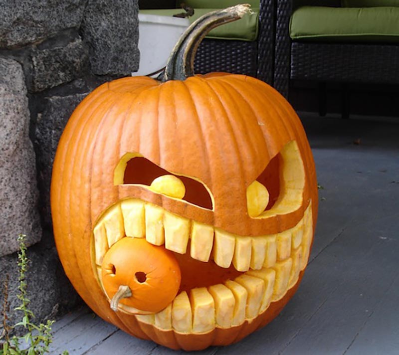 A pumpkin is carved to look like it's holding a smaller pumpkin in its teeth.
