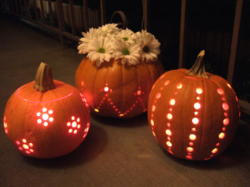 Three pumpkins have circular designs carved into them and one holds a boquet of flowers.