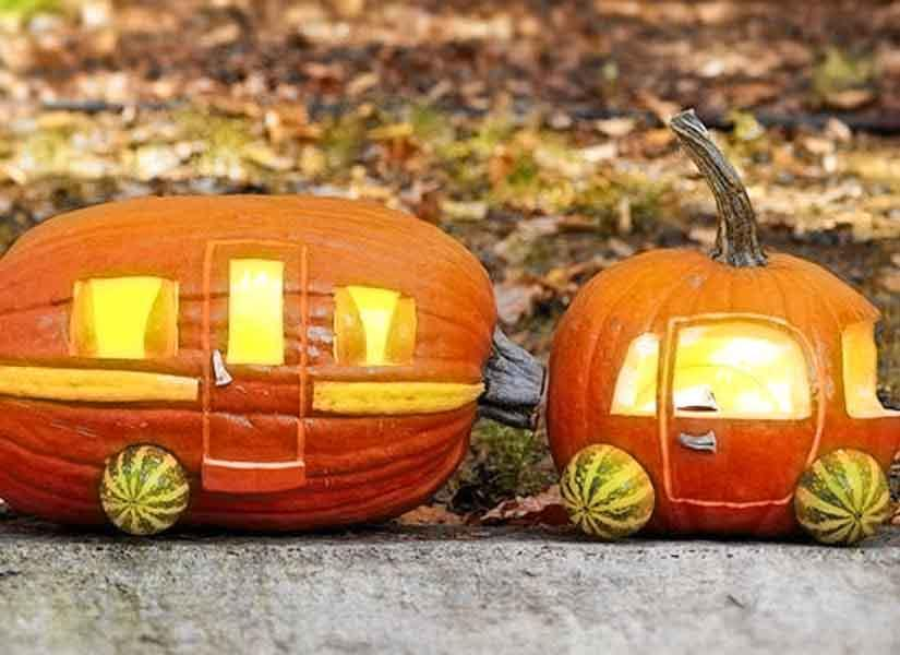 Two pumpkins are placed next to one another and designed to look like a camper.