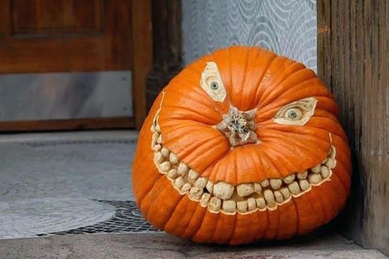 A pumpkin is carved with a large smile and beady, crazed eyes.