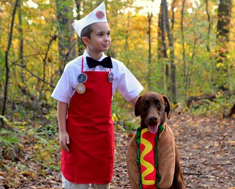 Boy dressed as a hot dog vendor with dog dressed as a hot dog