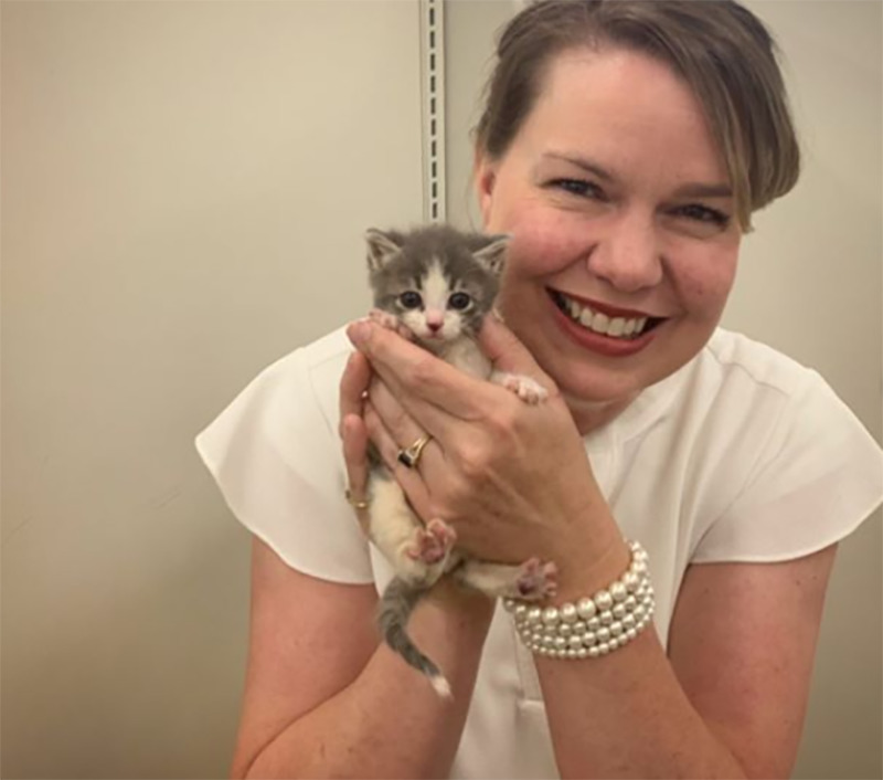 Cindy smiles while holding a kitten