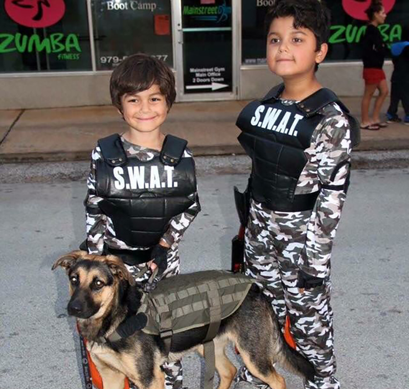 Two kids with dog in SWAT Halloween costumes