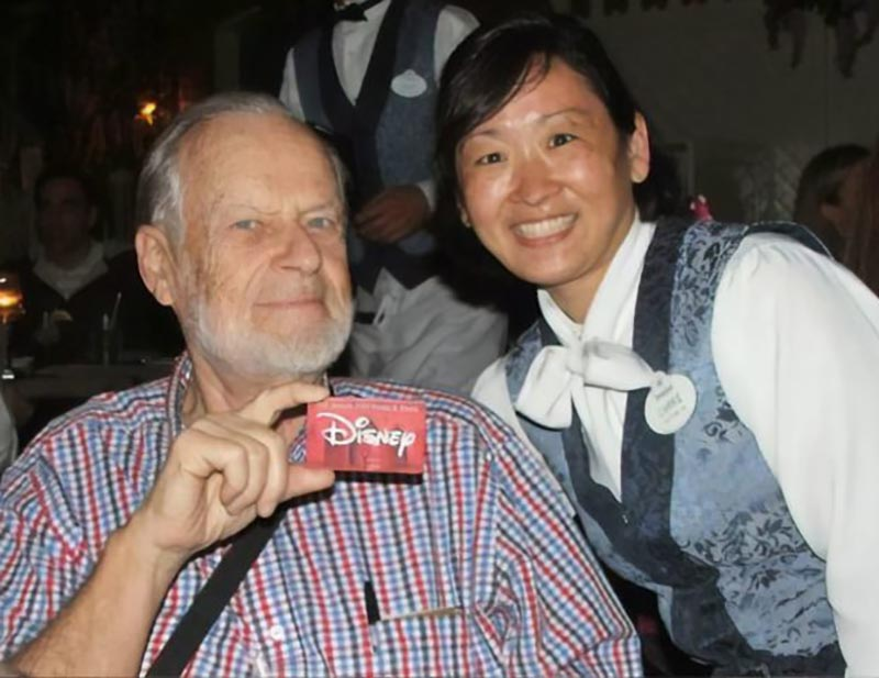 Dave poses with a Disney crew member while holding up his Disney pass.