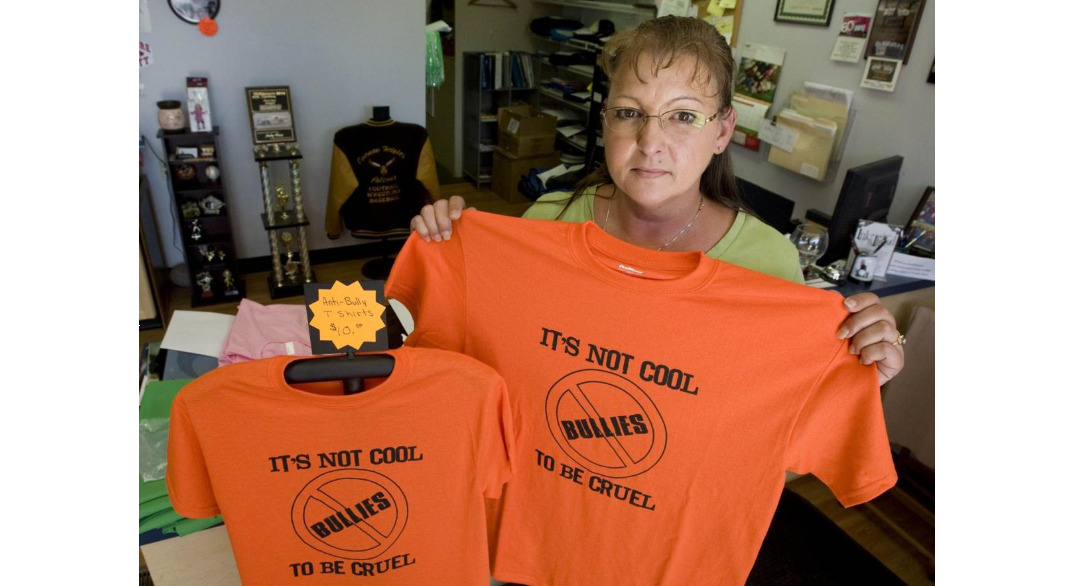 A woman holds up an orange anti-bullying shirt.