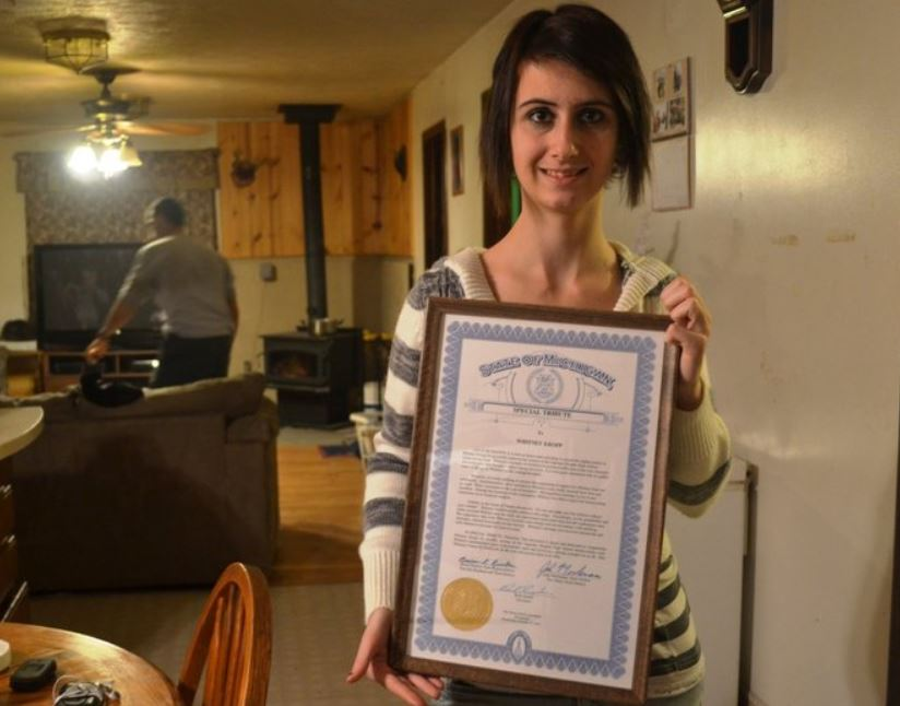 Whitney smiles while holding up a certificate.