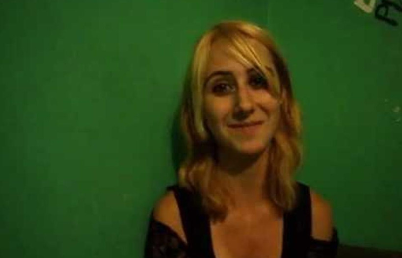 Whitney wears a small smile in front of a green wall.