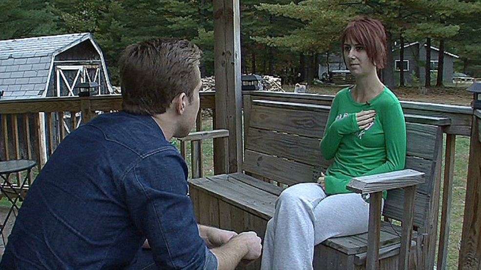 Whitney sits on a park bench and speaks to a journalist.