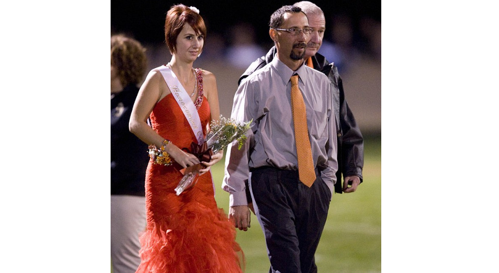 Whitney walks the Homecoming field with her dad.
