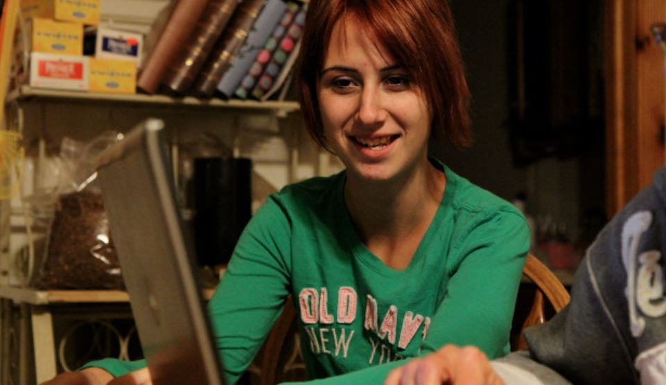 Teenage Whitney has short, red hair and looks at a laptop.