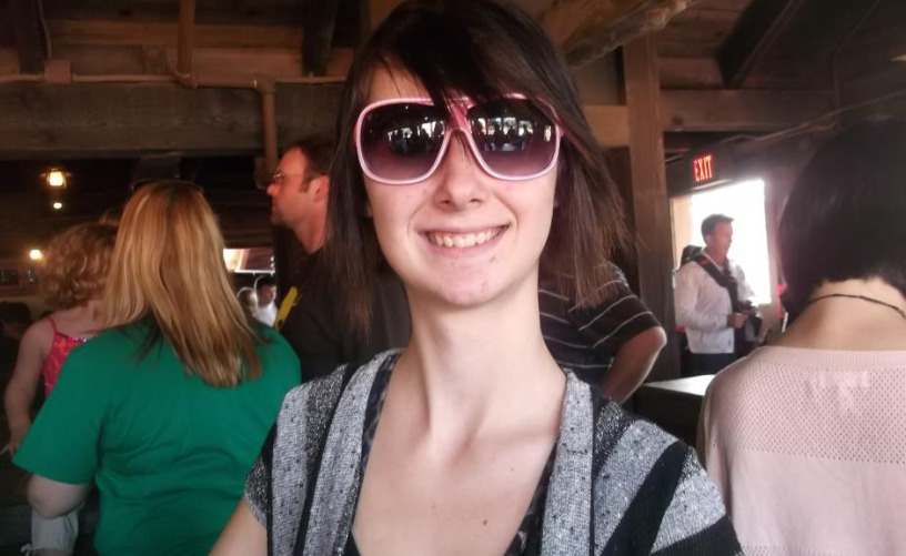Whitney wears short, brown hair and pink sunglasses.