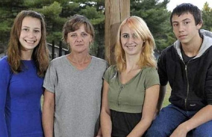 Whitney now has longer, blonde hair and is posing next ot her family.