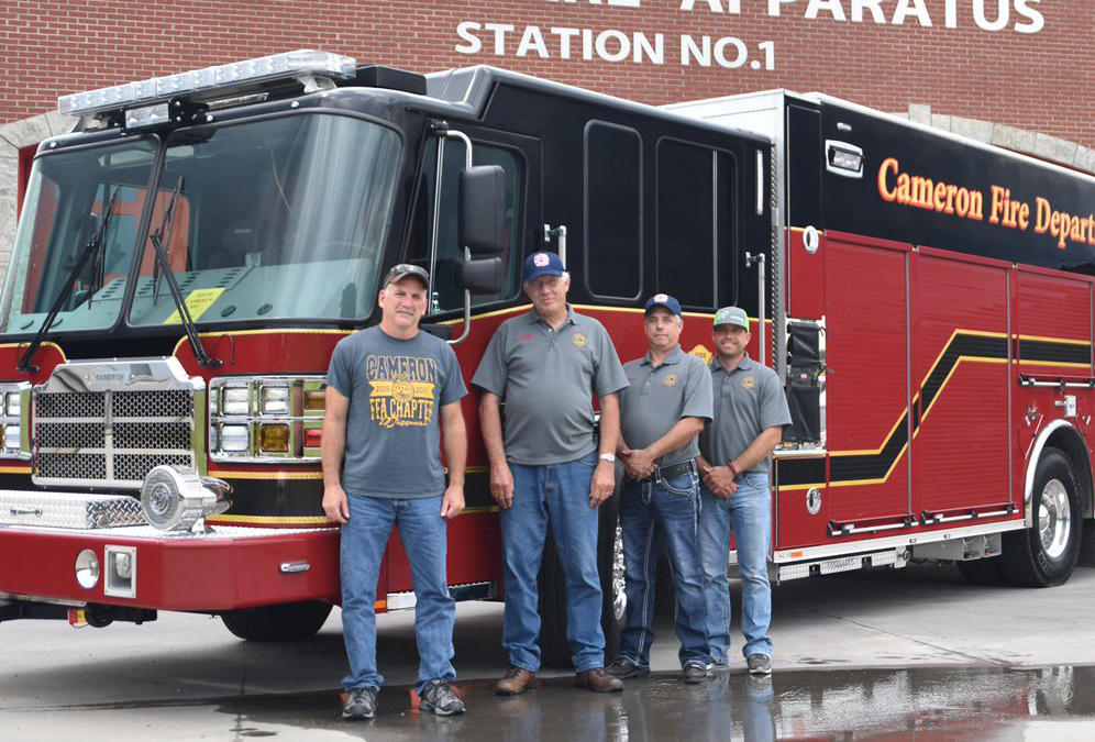 Firefighters from Cameron, Missouri stand in front of a firetruck.