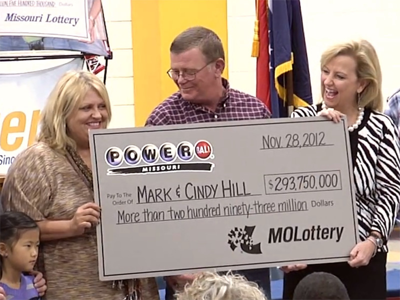 Cindy and Mark Hill hold up their lottery check happily with a representative.