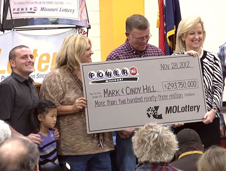 Cindy and Mark Hill hold up a lottery check for $293.75 million.