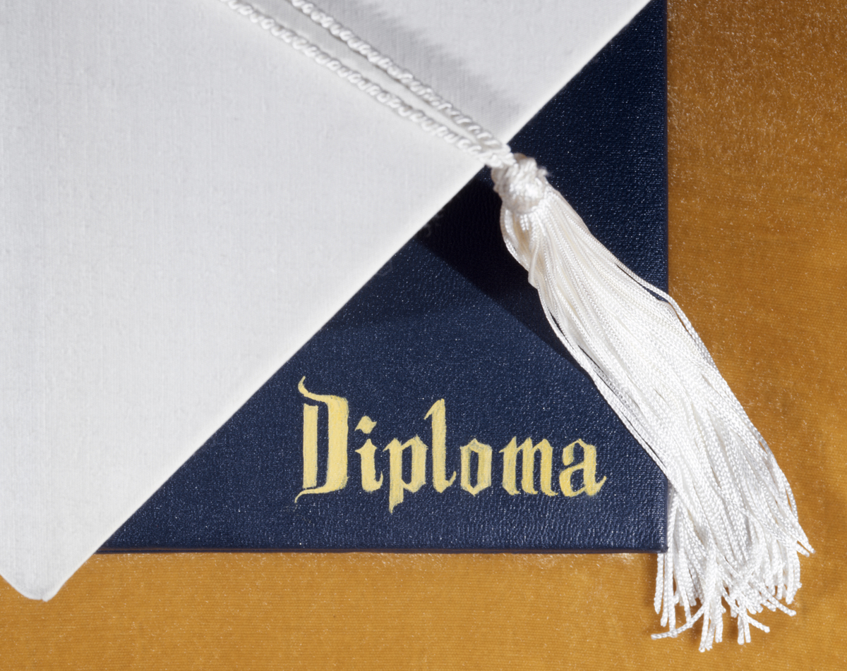 A white graduation cap sits atop a diploma.