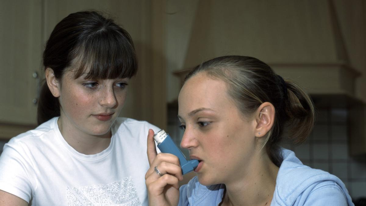 14 year old girl having asthma attack using inhaler