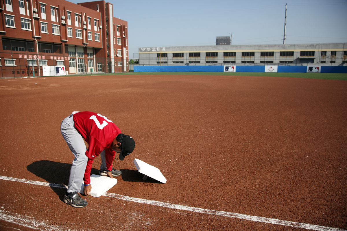 A student player installs a base on a baseball field.