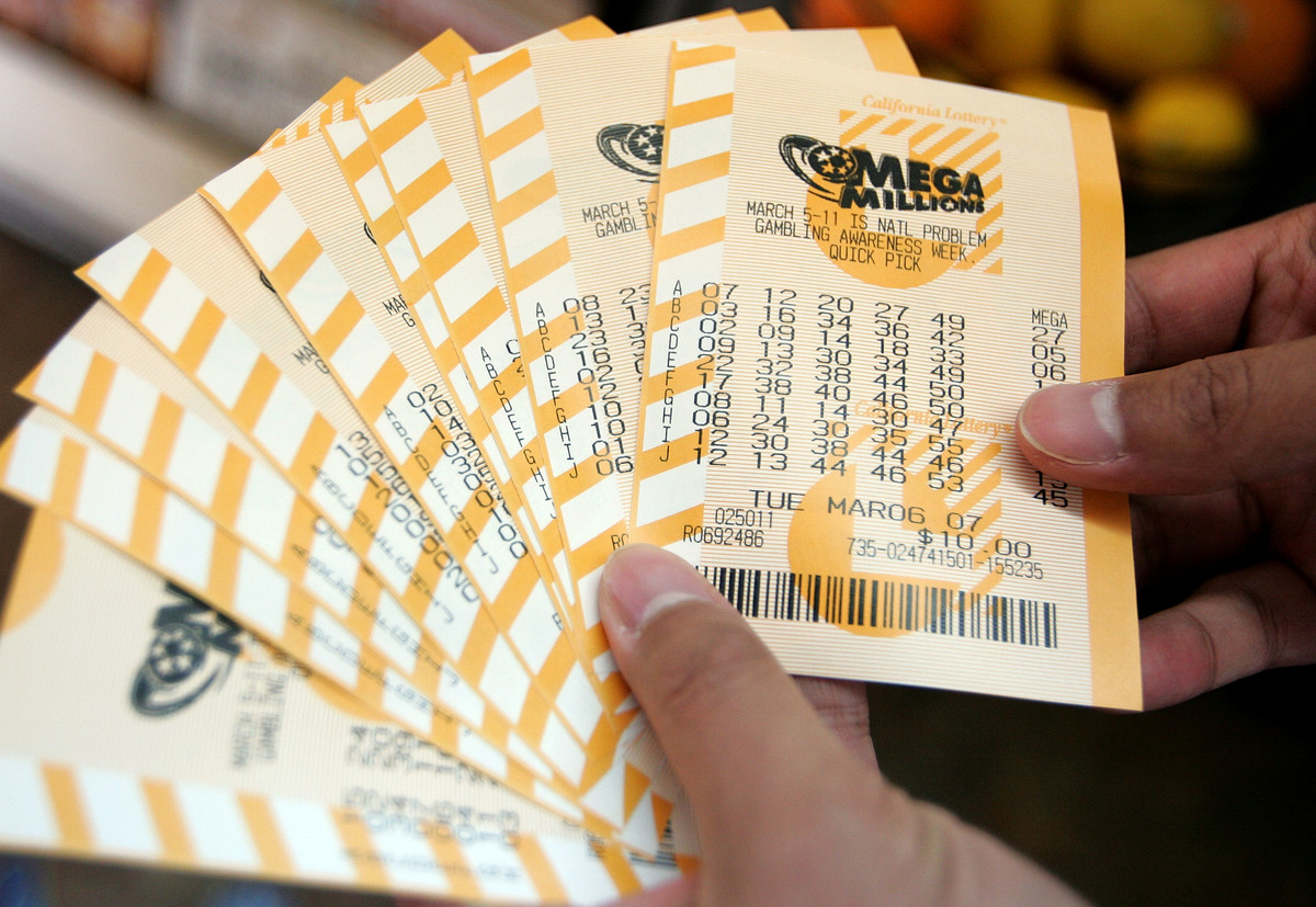 A man holds a bundle of Mega Millions lottery tickets.