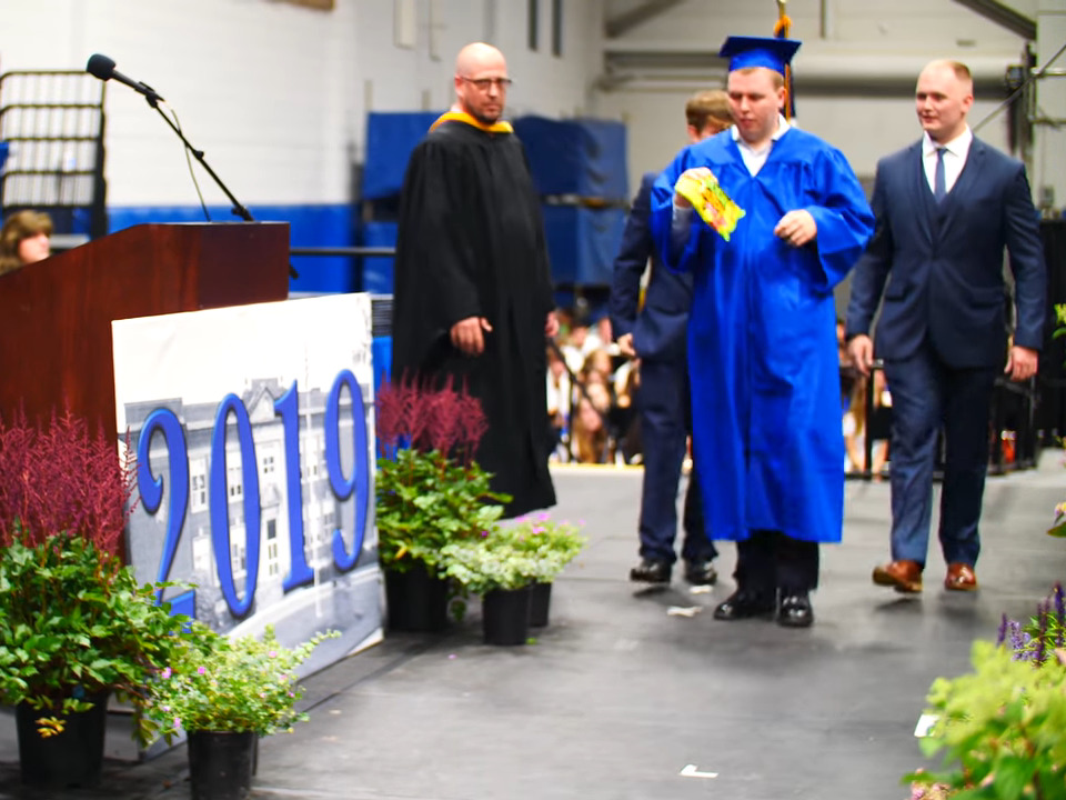 Jack Higgins walks off the graduation ceremony stage with his two brothers.