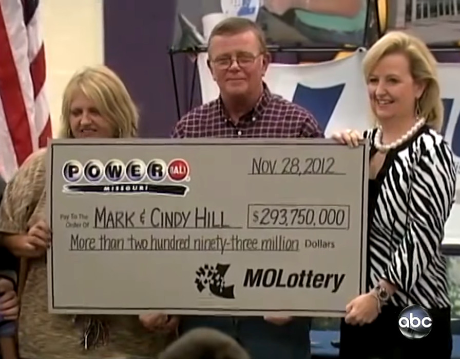 Cindy, Mark, and a spokesperson for the lottery hold up a $293 million check.
